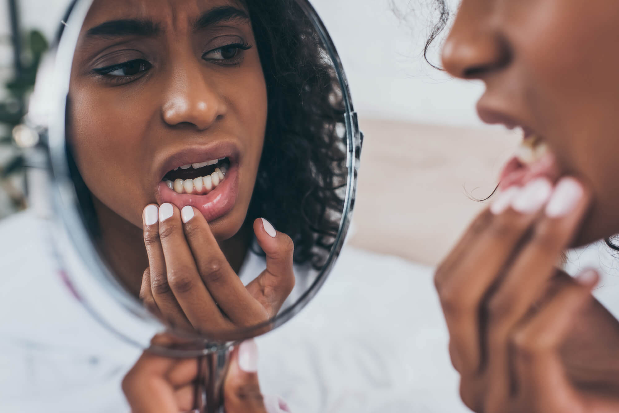 Woman looking at her gums in the mirror at the periodontist in north Miami